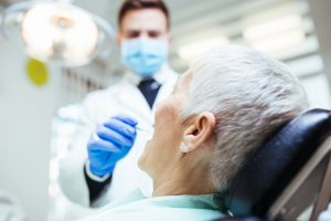 Dentist performing a TMD examination on older woman
