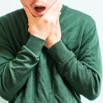 Man wearing a green shirt grasping his face due to TMJ pain