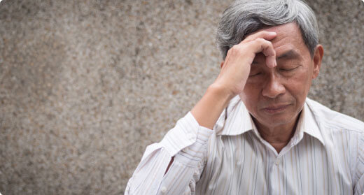 Older gentlemen touching his forehead with migraine pain
