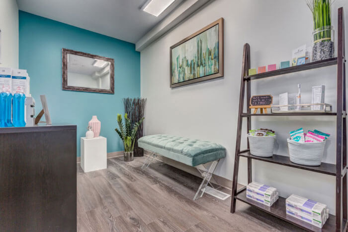 photo of Dr. Dahan's office with a teal wall, merchandise, and a bench